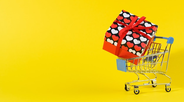 Red gift box with a red silk bow in a miniature metal trolley on a yellow surface. party backdrop, surprise, seasonal sale