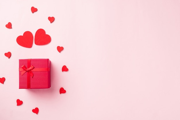 愛のためのリボンの弓と木製の赤いハート型の構成グリーティングカードと赤いギフトボックス
