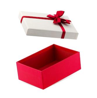 Красная подарочная коробка с лентой, изолированной на белом фоне с обтравочным контуром.