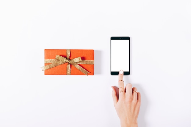 Red gift box with ribbon and mobile phone