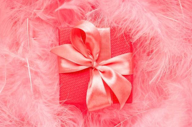羽で作られたパステルピンクの背景にサテンの弓と赤いギフトボックス。