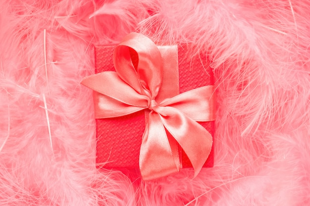 Red gift box with satin bow on pastel pink background made of feathers.