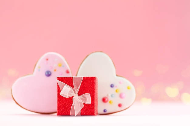 ピンクの背景にバレンタインデー、母の日、誕生日の2つのハート型のジンジャーブレッドが付いた赤いギフトボックス。