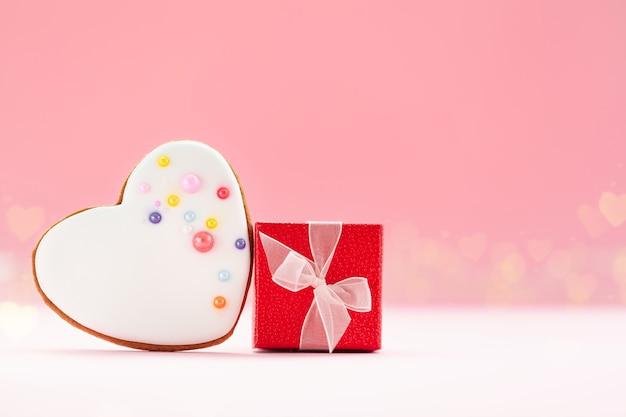 ピンクの背景にバレンタインデー、母の日、誕生日のための白いハート型のジンジャーブレッドと赤いギフトボックス。