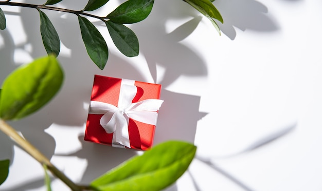 Red gift box with white ribbon on white table under spring flowers with shadow . top view and copy space