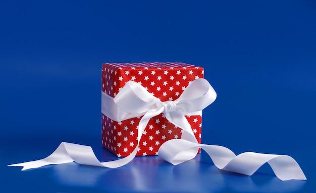 Красная подарочная коробка с белым бантом из атласной ленты