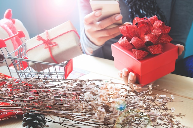 Red gift box on woman hand, using mobile phone. holiday concept