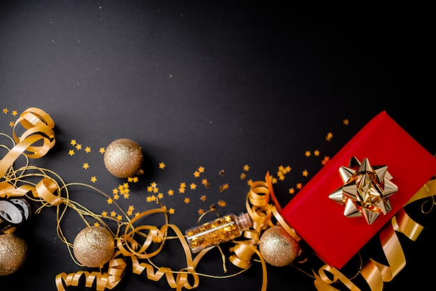 Red gift box for women with golden bow on black