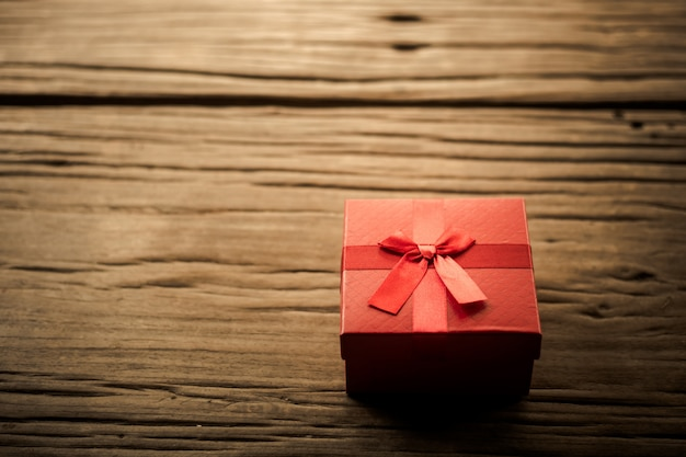 Red gift box on wooden plank.