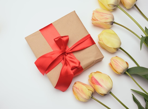 Red gift box and yellow tulips on white surface, festive surface, top view