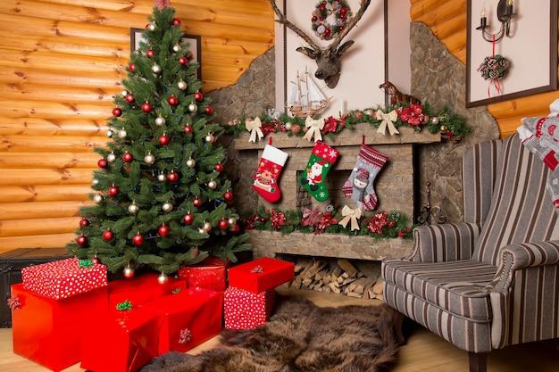 Красные подарочные коробки и украшенная красочными шарами елка у камина с рождественскими чулками