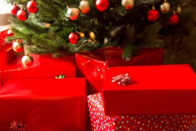 Красные подарочные коробки и украшенная красочными шарами елка, крупным планом
