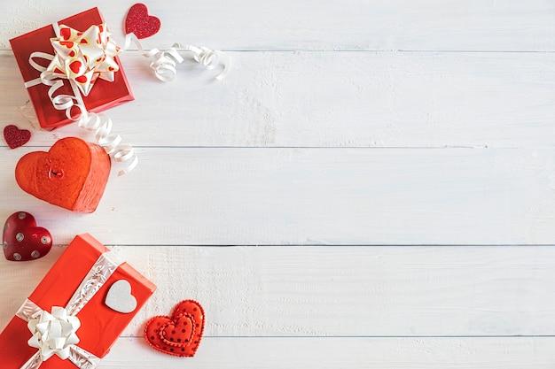 Красные подарочные коробки и маленькие сердечки на белом деревянном фоне, вид сверху, концепция валентина