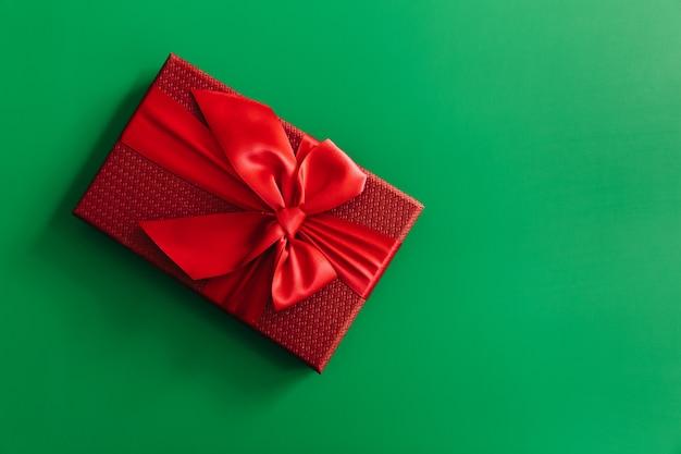 緑の背景に赤いギフトボックス。クリスマスカード。フラットレイ。テキスト用のスペースがある上面図。