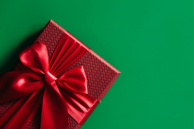 녹색 배경에 빨간색 선물 상자입니다. 크리스마스 카드. 평평하다. 텍스트를위한 공간이있는 상위 뷰.