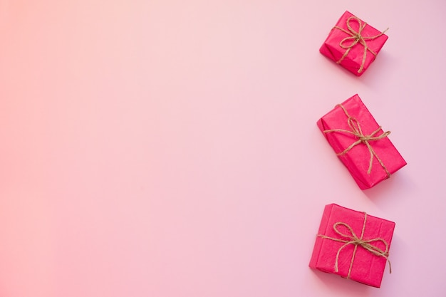 Red gift boxes on pink background.