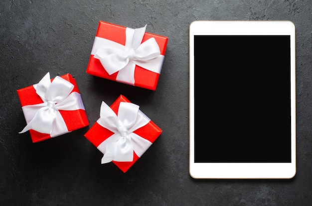 Red gift boxes and a tablet with a blank screen for text