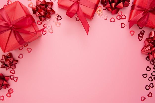 Красные подарочные коробки с лентой на розовой предпосылке, плоском положении, дне валентинки, космосе экземпляра.
