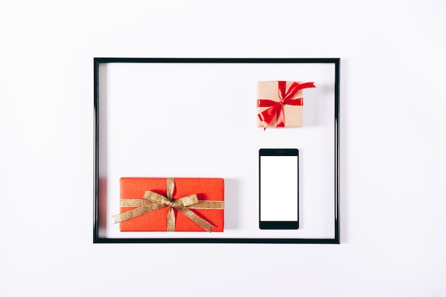 Red gift boxes with ribbons and mobile phone in a frame