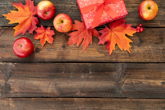 Red gift next to colorful leaves with copy space