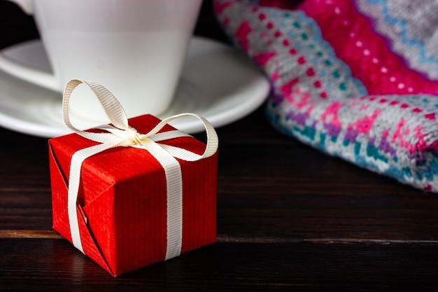 어두운 나무 테이블에 빨간색 선물입니다.