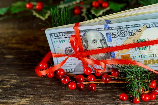 Red gift ribbon bow over american dollars. money background.