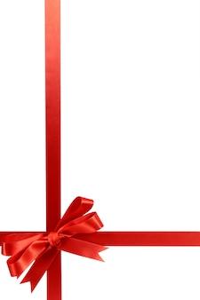 Red gift ribbon bow vertical corner border frame isolated on white.