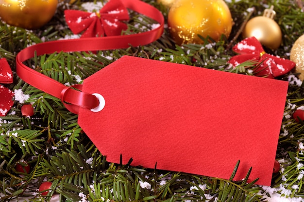 Red gift tag or price ticket with red ribbon on a christmas tree background
