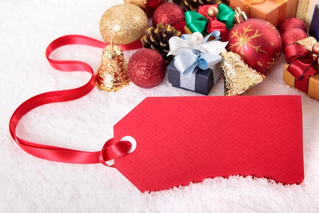 Red gift tag or price ticket with red ribbon in a snow background with gifts
