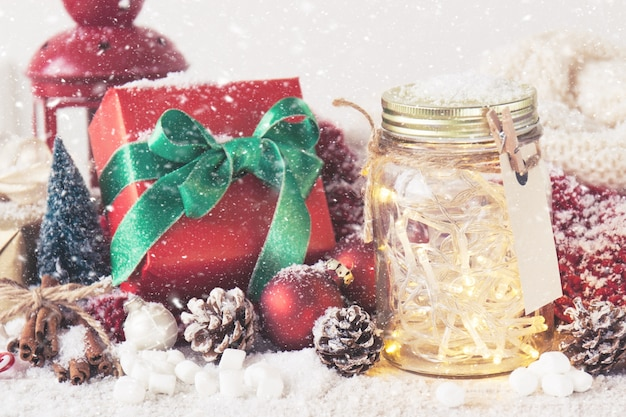 Red gift with green bow next to a glass jar with lights