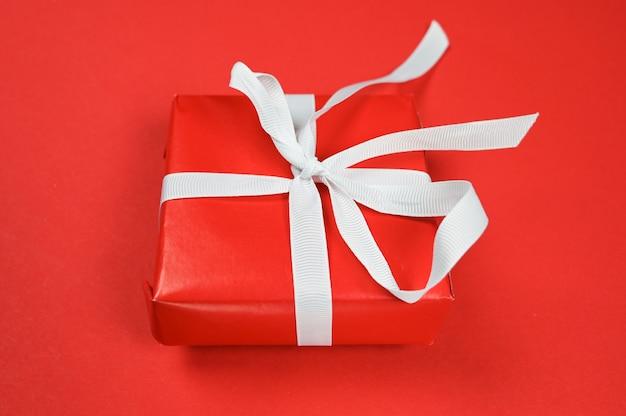Красный подарок с белой лентой на красной поверхности.
