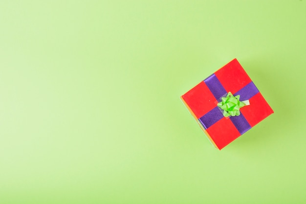 Red gift wrapped with blue and green ribbon over the green background