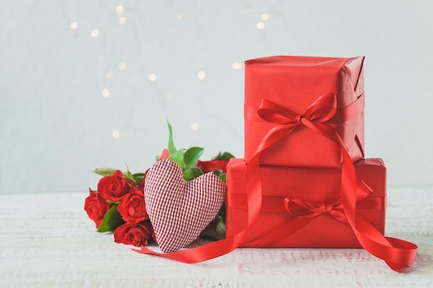Regali rossi con un mazzo di rose al lato