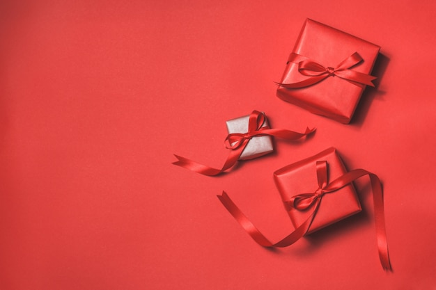 Red gifts with a red tie on a red background