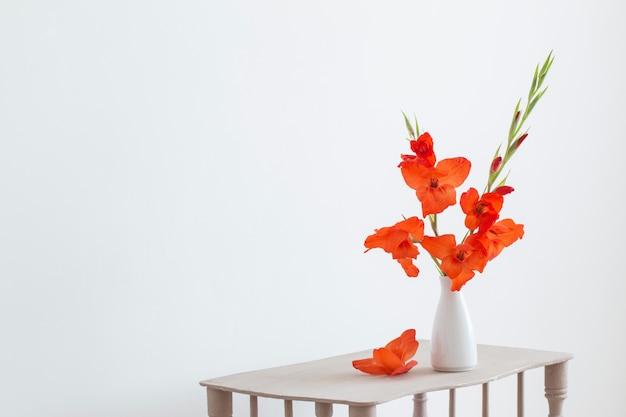 Красный гладиолус в вазе на столе