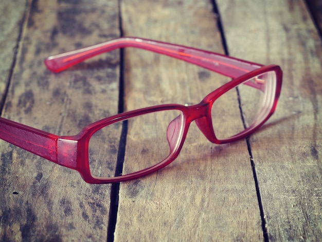 Red glasses on wood background retro-vintage style