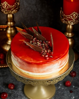 Red glazed cake with pomegranate and caramel triangles