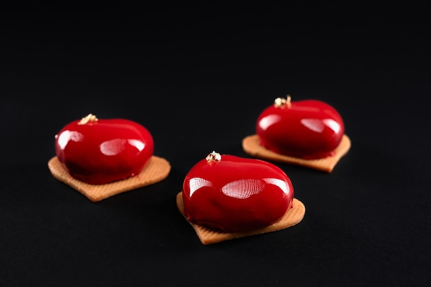 Red glazed heart cakes on cookies.