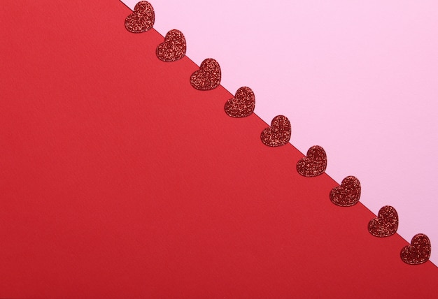 Red glitter hearts on pink and red background. romantic, st valentines day concept.top view.
