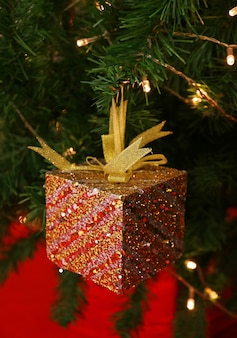 Red glitter square mini gift box with gold ribbon bow hanging on sparkling christmas tree
