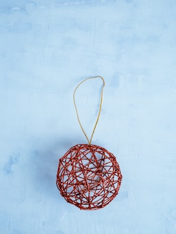 Red glitter toy for christmas tree on light blue background. copy space.