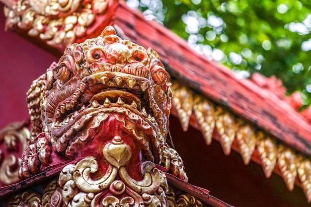 Статуя монстра из красного золота в азии на севере тайского храма. их ответственность - защита от плохого внешнего вида.