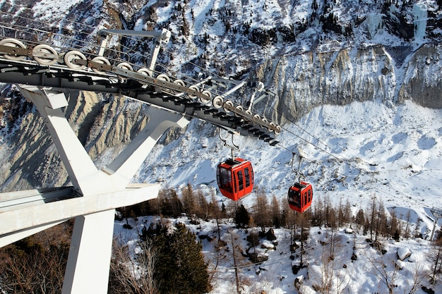 Red gondolas in alpine mountain in winter