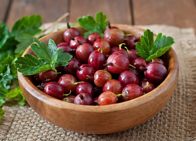 Red gooseberries in a wooden bowl