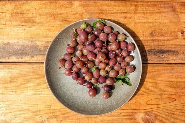 木製の背景の上の粘土板の赤いグーズベリーベリー。グーズベリーの茂みから夏に集められました。
