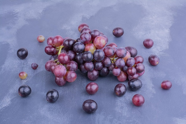 Acini di uva rossa isolati sul tavolo blu.