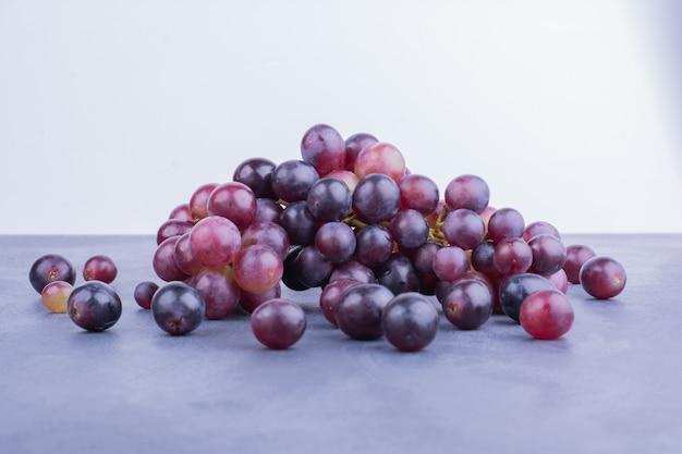 Красные ягоды винограда на синем.