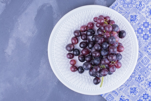 Red grape berries in a white plate.