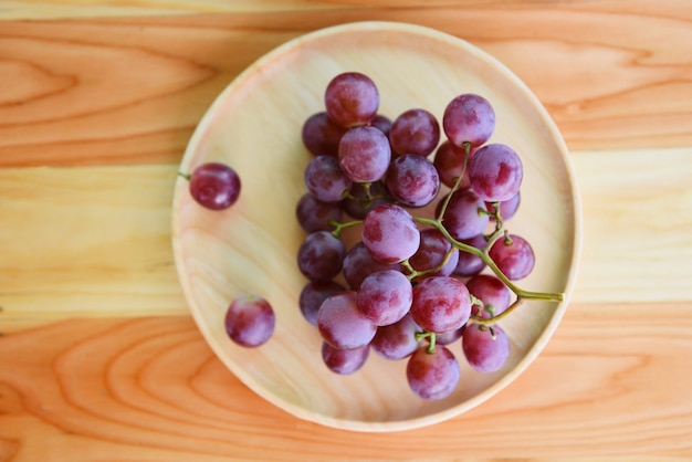 Red grape bunch on wooden plate on a table
