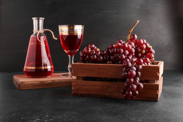 Red grape bunches in a wooden tray with a glass of wine on black.